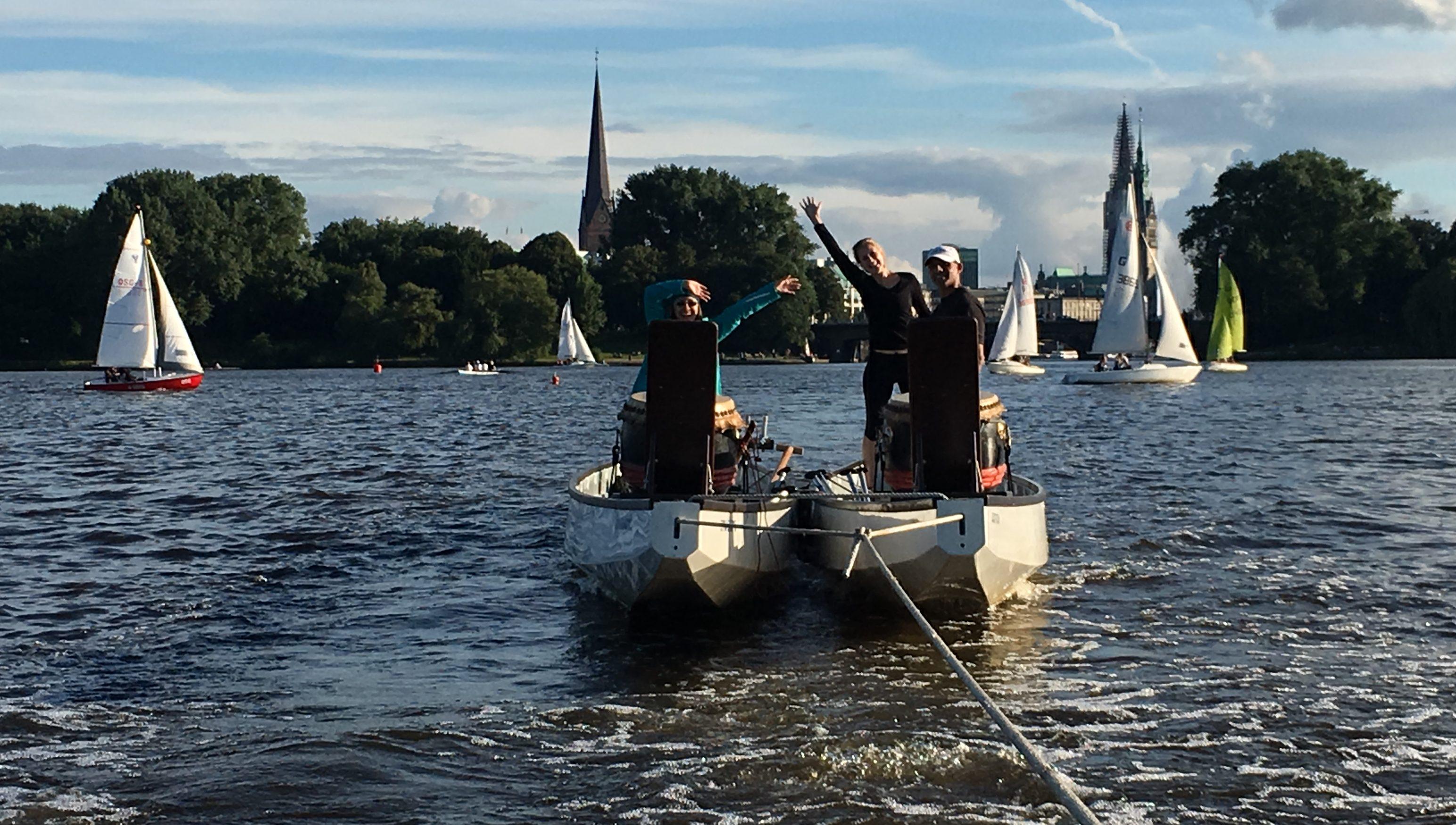 Drachenboote werden über die Alster zum Anleger Hamburg geschleppt